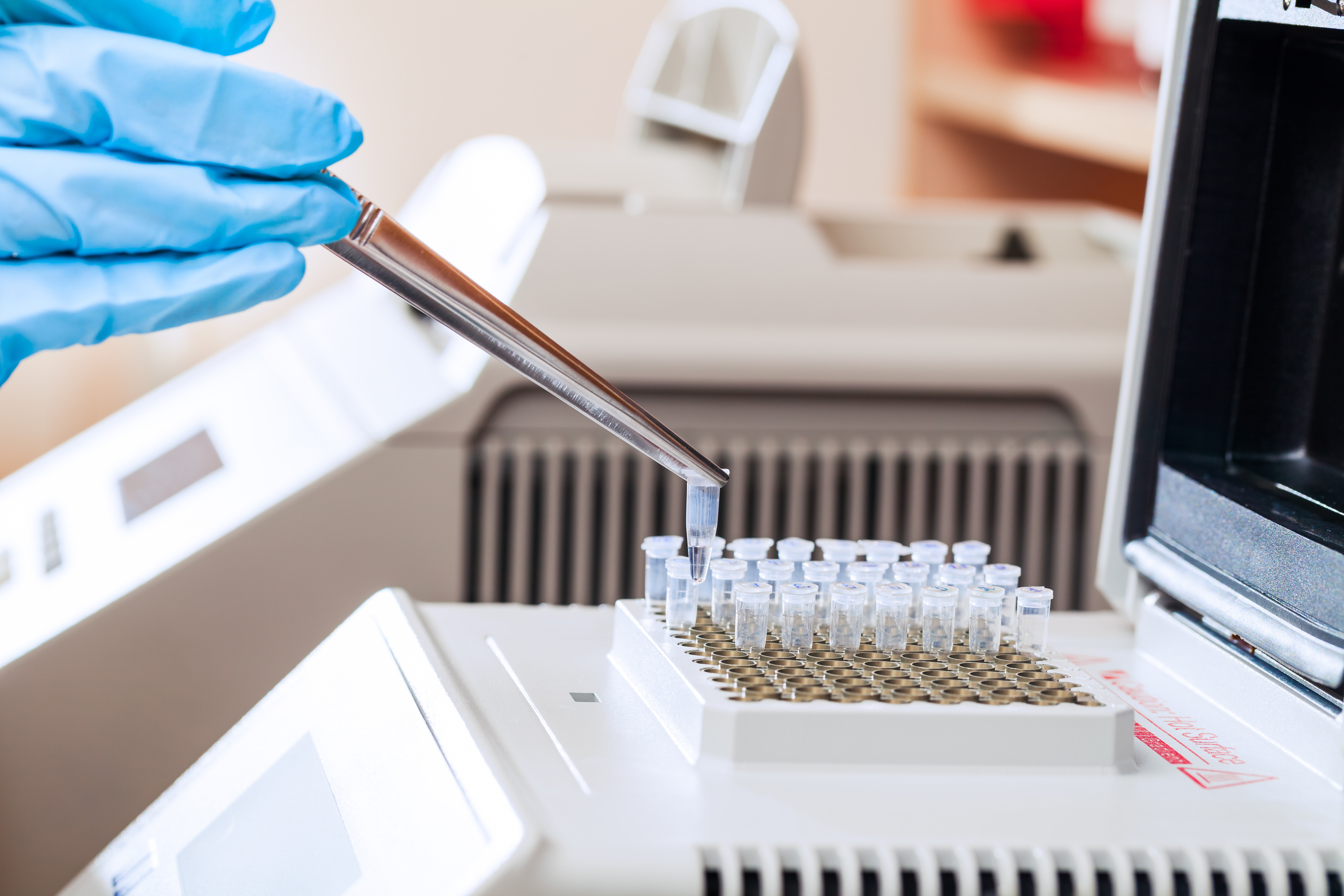 Technician Loading Test Tubes with Sampled DNA for Polymerase Chain Reaction